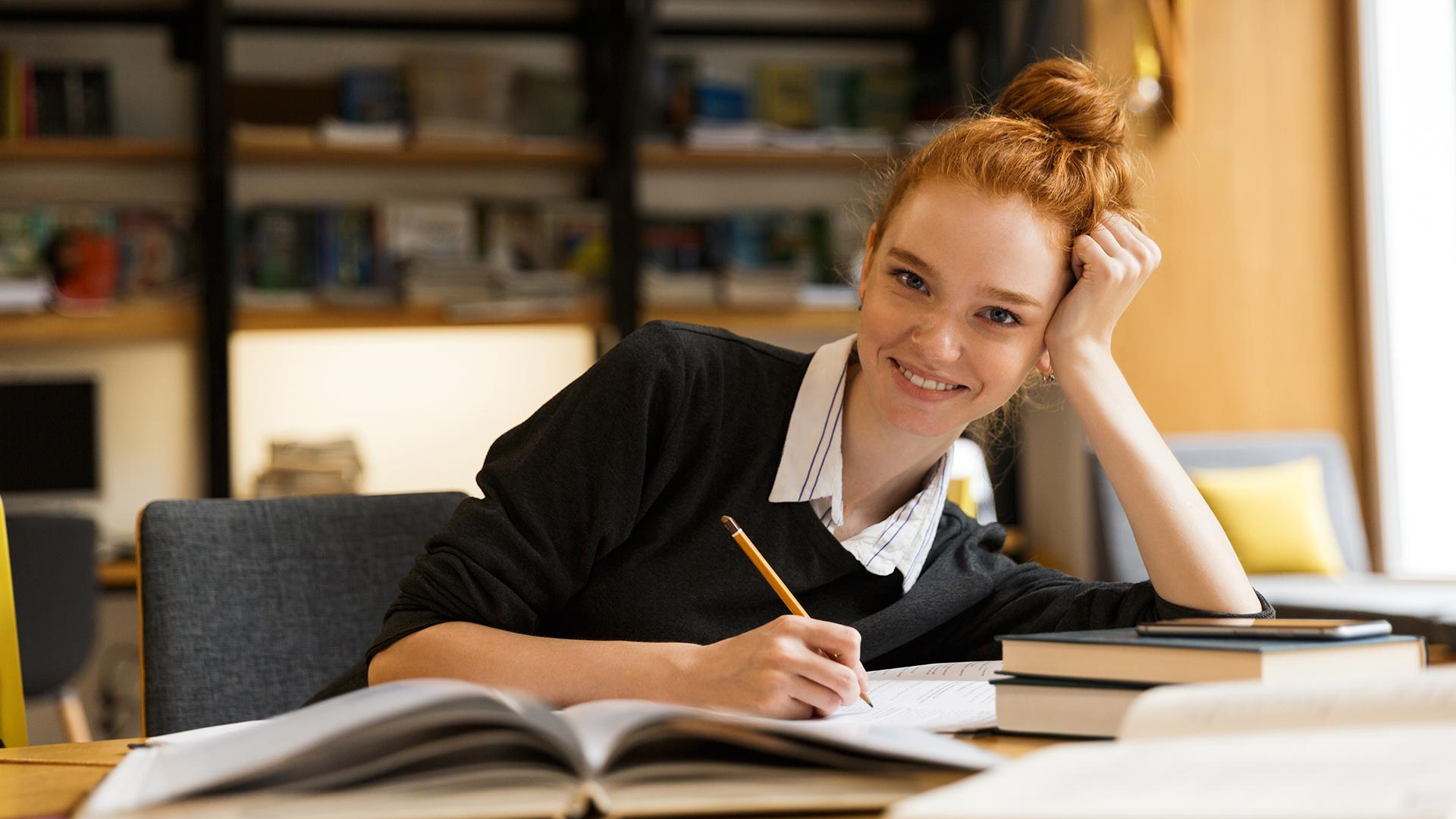 Gedächtnistraining: Junge, glückliche, rothaarige Schülerin/Studentin sitzt in der Bibliothek um ihr Gedächtnis fit zu halten