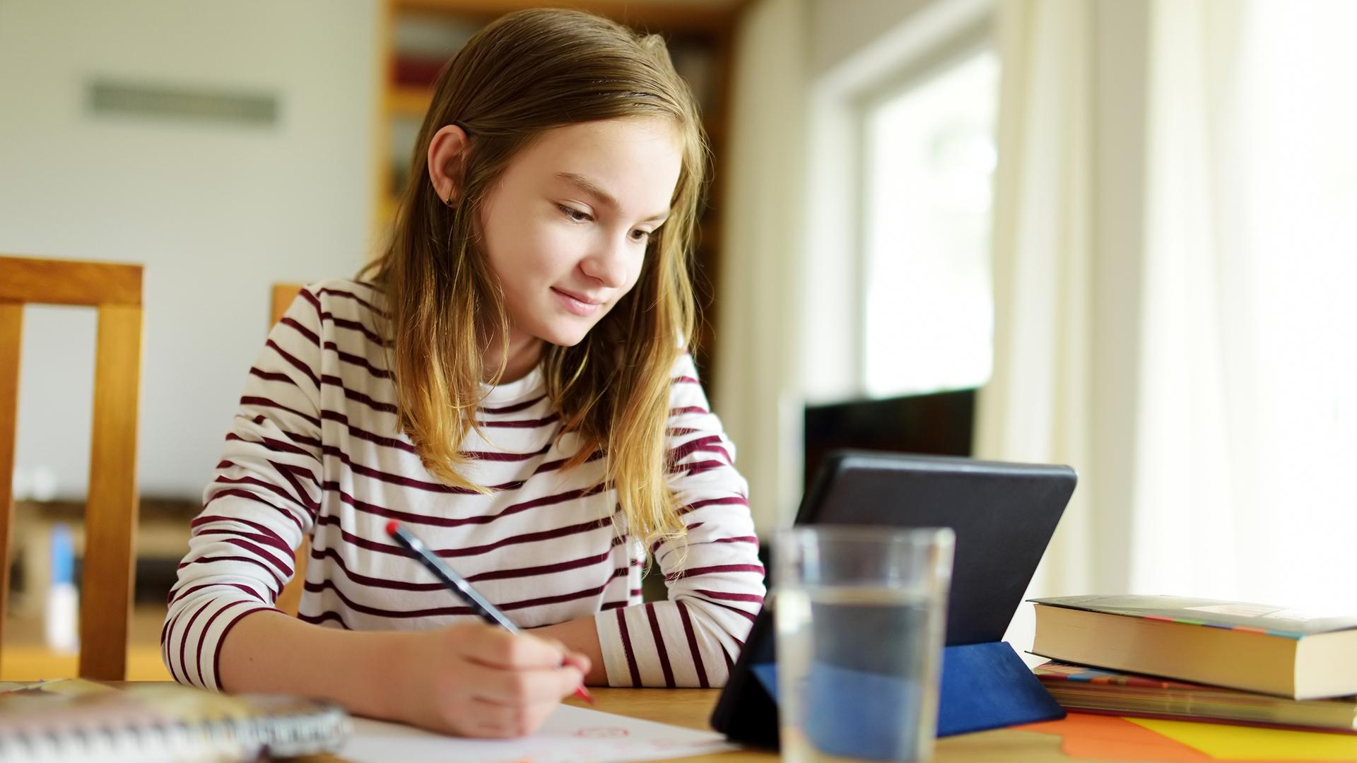 Junge Schülerin nutzt Online Lernbetreuung am Tablet